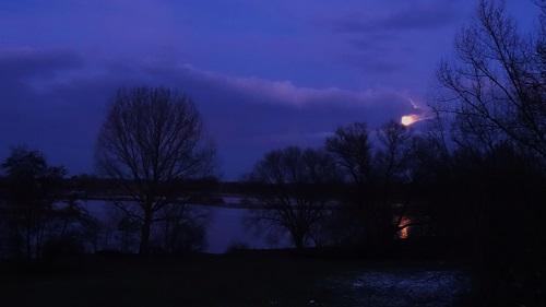 De maan komt even tevoorschijn tussen de wolken